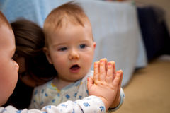 婴孩握他的在镜子的手和由反射惊奇 免版税库存图片