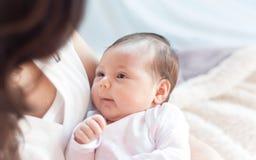 婴孩新出生她的母亲 母亲抱着她的小婴孩 库存照片