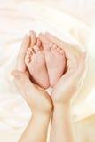 婴孩新出生的脚在母亲手上 美好的新出生的孩子脚,家庭爱概念 免版税库存图片