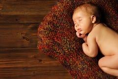 婴孩新出生的画象,睡觉在褐色的孩子 免版税库存照片