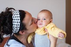 婴孩是完全地愉快的听到她i,如果亲吻母亲的图象感谢使用会您的地方 免版税库存照片
