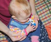 婴孩是病与在老鼠的一个温度计在我的妈妈` s手上 免版税库存照片