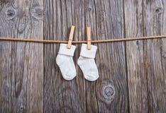 婴孩晒衣绳货物停止 在晒衣夹的婴孩白色袜子 免版税库存图片
