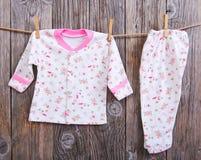婴孩晒衣绳货物停止 婴孩女衬衫和裤子滑子在晒衣夹在绳索 免版税库存照片