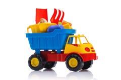 婴孩海滩被隔绝的沙子玩具和五颜六色的塑料卡车 免版税库存图片