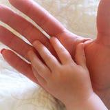 婴孩特写镜头递基于母亲或祖母手 免版税库存图片