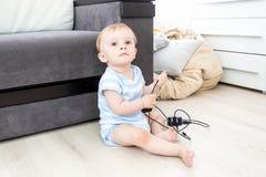 婴孩的概念处于危险中 男婴坐单独地板和p 免版税图库摄影