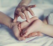 婴孩的脚在手上 免版税库存照片