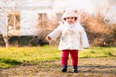 婴孩盖帽与耳朵新出生的走的公园冬天穿戴了第一个ste 免版税库存照片