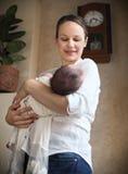 婴孩睡着在她的母亲的胳膊 免版税库存图片