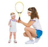 给婴孩网球拍的母亲 库存图片