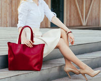 婴孩背景机体现有量一点在部分白色 女孩坐有一个大红色超级时兴的提包的台阶在礼服和宽适合的针对性的脚跟 免版税库存照片