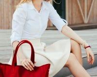 婴孩背景机体现有量一点在部分白色 女孩坐有一个大红色超级时兴的提包的台阶在礼服和宽适合的针对性的脚跟 图库摄影