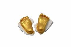 婴孩脚印刷品在石膏的金子颜色 免版税库存图片