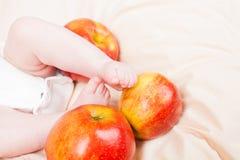 婴孩腿和红色成熟苹果 免版税图库摄影