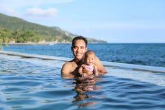 婴孩获得乐趣在与母亲的游泳池 库存照片