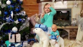 婴孩跳舞和有乐趣在装饰的大树的圣诞夜期间充分五颜六色的闪耀的光前面 股票录像