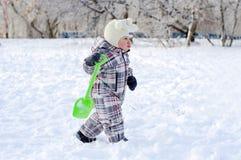 婴孩蹒跚与铁锹在冬天 免版税库存图片