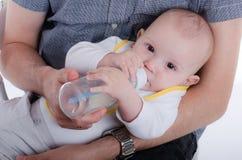 婴孩饮用的瓶牛奶 免版税库存照片