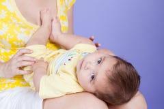 婴孩说谎我的她的膝盖的母亲 免版税库存照片