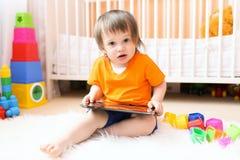 婴孩画象有片剂计算机的 库存照片