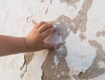 婴孩` s手接触老被打碎的膏药墙壁 免版税图库摄影