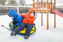 孪生演奏与可膨胀的爬犁的降雪时间 库存照片