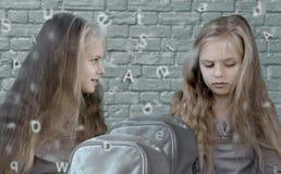 孪生 一个砖墙的背景的两个逗人喜爱的女孩有字母表的 免版税图库摄影
