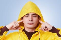 宁静的可爱的男性闭上眼睛并且塞住耳朵,尝试集中,并且听不到喧闹声,佩带在头, isola的黄色敞篷 库存图片