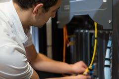 它工作在网络服务系统和电缆上的技术人员 免版税库存照片