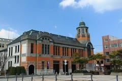 它开户立场在蓝天下在福冈,日本 它是银行的大厦100年前, 图库摄影