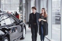 它是我要的这一辆汽车!站立在经销权的美好的年轻夫妇选择汽车买 免版税图库摄影