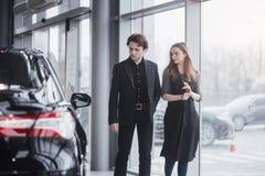 它是我要的这一辆汽车!站立在经销权的美好的年轻夫妇选择汽车买 库存照片