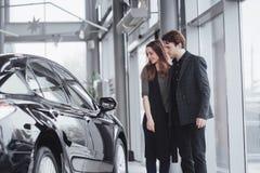 它是我要的这一辆汽车!站立在经销权的美好的年轻夫妇选择汽车买 库存图片
