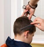 它的一种新的发型的时刻 在美发师的手上有梳子和剪刀 在美发师孩子的理发 免版税库存照片