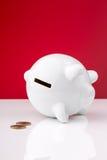 它的旁边红色背景的白色存钱罐 免版税库存照片