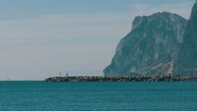 它美丽的波浪的地中海,打反对白色沙子和直布罗陀的岩石反对背景 影视素材