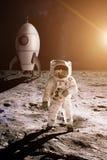 宇航员在玩具火箭背景的月亮走  库存照片