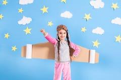 宇航员服装的小孩女孩是使用和作梦成为太空人 免版税库存图片