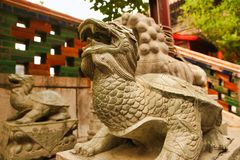 守卫亭子的龙儿子在和平和和谐庭院  北京瓷 免版税库存照片