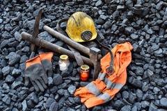 守夜光,与矿工财产盔甲的蜡烛,手套,镐,背心,传送带 图库摄影