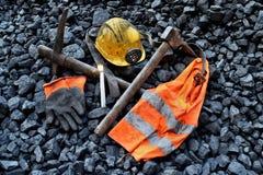 守夜光,与矿工财产盔甲的蜡烛,手套,镐,背心,传送带 库存照片