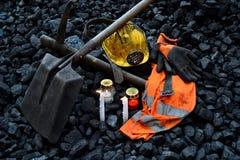 守夜光,与矿工财产盔甲的蜡烛,手套,镐,铁锹,背心,传送带 图库摄影