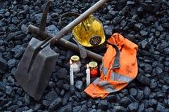 守夜光,与矿工财产盔甲的蜡烛,镐,铁锹,背心,传送带 免版税图库摄影