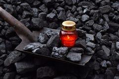 守夜光,与矿工财产镐,铁锹的蜡烛 图库摄影