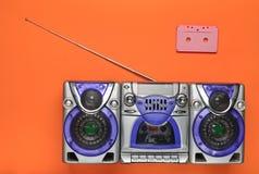 守旧派减速火箭的录音机和卡型盒式录音机在橙色背景 过时技术 简单派趋向  顶视图 库存照片