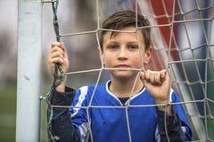 守门员制服的小男孩在滤网在体育场的橄榄球目标后 免版税库存图片