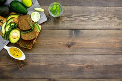 安全减重的早餐 鲕梨多士用黑麦面包,石灰、橄榄油和绿色在黑暗的木背景冠上 图库摄影