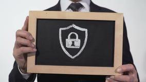 安全在黑板得出的挂锁象在商人手上,抗病毒安全 影视素材