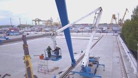安全地安装细节的两名工作者在起重机 夹子 两名工作者修理在站点的起重机 股票录像